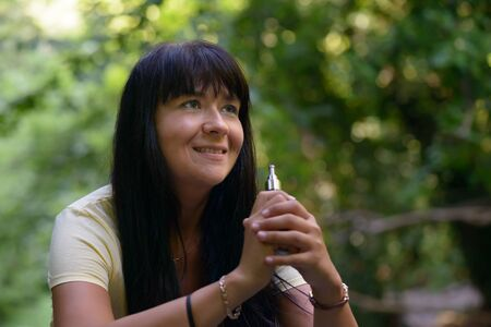 smocking: Nice girl smiling and smocking an electronic cigarette in the wood Stock Photo