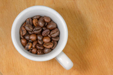 Nice cup of coffe with toasted coffee seeds inside on wood background