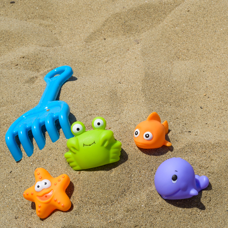 children crab: funny and colorful plastic toys on the beach Stock Photo