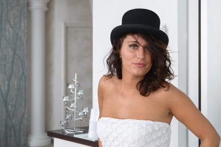 Una linda chica en blanco posando con un sombrero negro Foto de archivo - 80420708