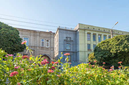 building with communism symbol behind flowers