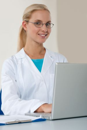 Beautiful female doctor working on her laptop Stock Photo - 6207380