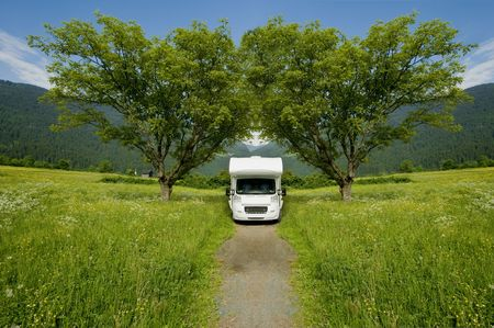 motor home: Caravan in a park, mountqins in the background