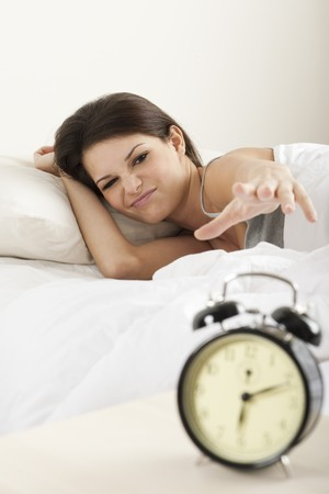 morning routine: Young woman waking up in the morning , trying to put off an alarm clock