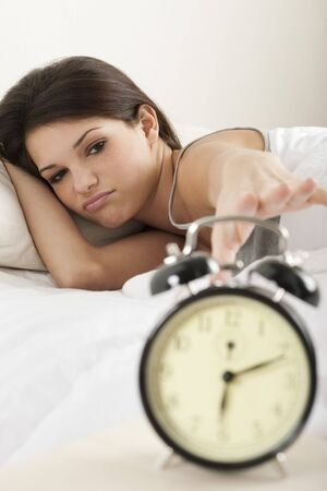 Young woman waking up in the morning , trying to put off an alarm clock photo