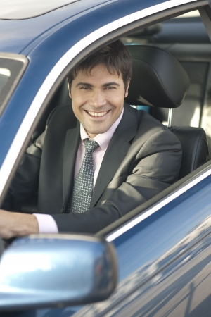 Smiling businessman driving car photo