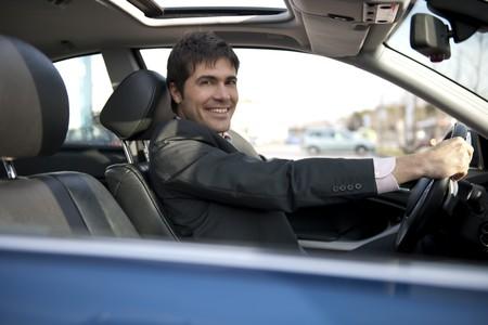 Smiling businessman driving car photo