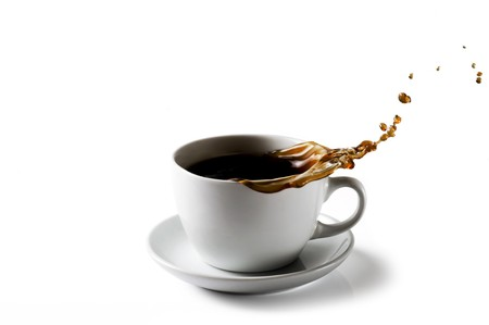 A cup of coffee with splashing coffee pouring out on to a white background photo