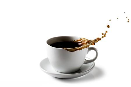 d�bord�: Une tasse de caf� avec �claboussures versant caf� out sur � un arri�re-plan blanc  Banque d'images