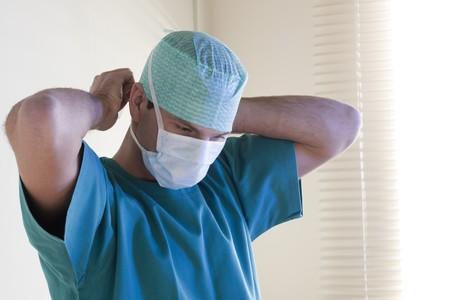 Male surgeon tying mask Stock Photo - 7275624