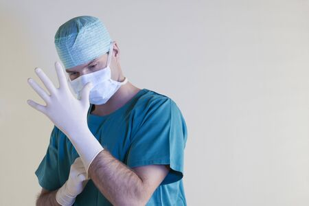 Surgeon  putting gloves on gloves on photo