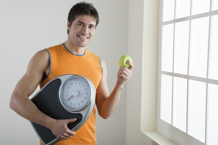 Sportsman holding scale and apple; concept: healthy lifestyle photo
