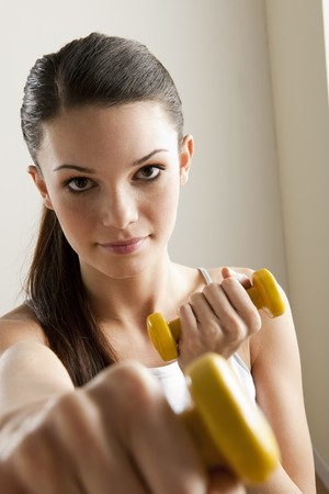 Young woman excercising with dumbells photo