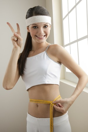Young woman looking excited for her successful diet Stock Photo - 7325707