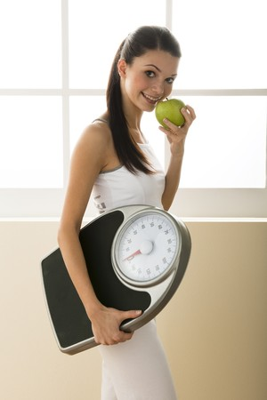 vertica: Young woman holding weight scale Stock Photo