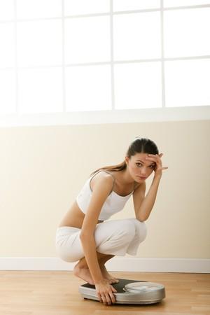 gewicht skala: Traurig Teenager-M�dchen auf die Waage. Konzept: teenage Di�t Probleme.  Lizenzfreie Bilder