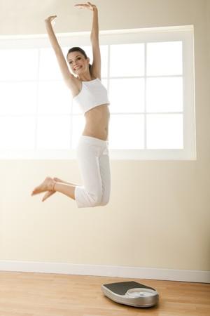 gewicht skala: Begeistert junge Frau springen, Waage auf dem Boden.  Lizenzfreie Bilder