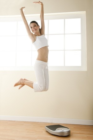 Excited young woman jumping, weight scale on the floor. photo