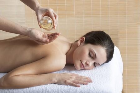 olio corpo: Bella donna rilassata che riceve un massaggio alla schiena con olio