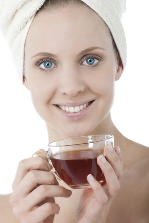 Beauty wrapped in towel with herbal tea photo
