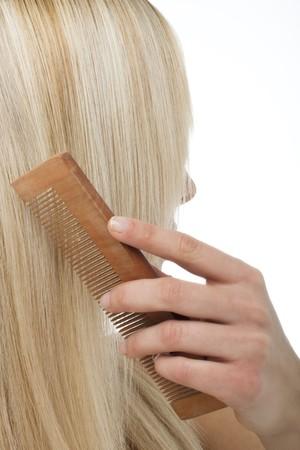 Beautiful blonde woman brushing her hair photo