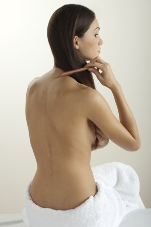 combing hair: Young woman combing her hair