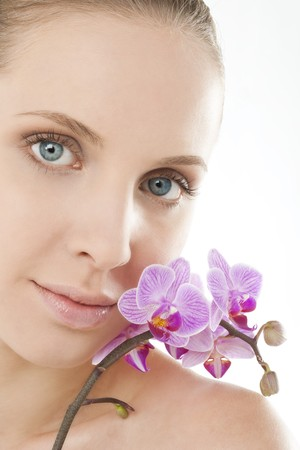Close-up of a beauy with an orchid next to her face photo