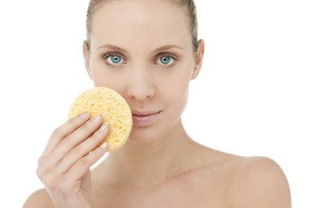 Beautiful blond woman with sponge for make-up removing photo