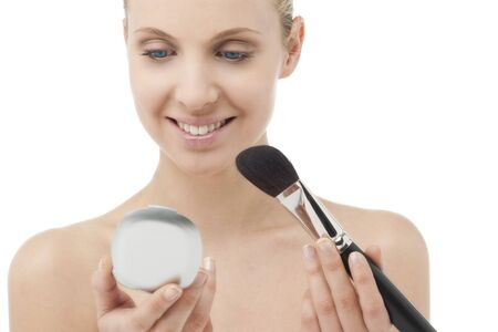 Woman with powder brush and mirror photo