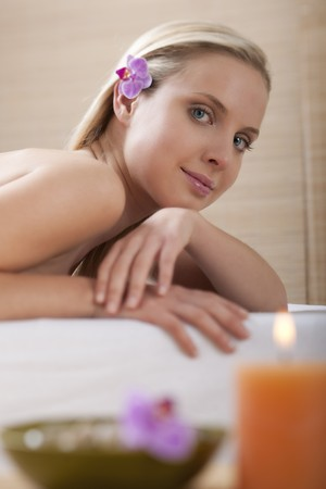Close-up of a young beautiful woman at spa, focus on background photo