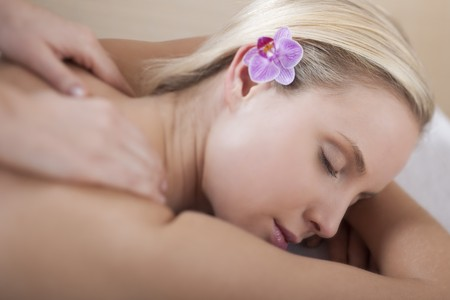 Young woman receiving back massage, selective focus photo