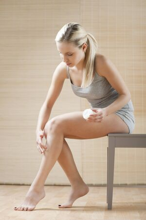 Young woman applying moisturizer Stock Photo - 7368981