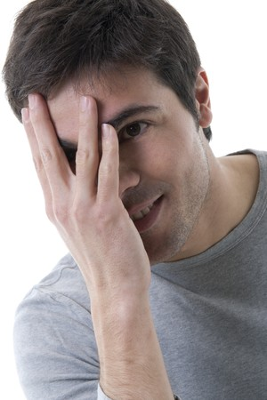 embarassment: Young shy man with hand over his face
