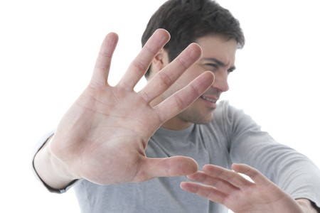 embarassment: Young man  with hands outstretched, warding off any unwelcome situations Stock Photo