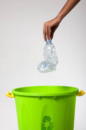 putting green: Womans hand putting a plastic bottle into a recycling bin