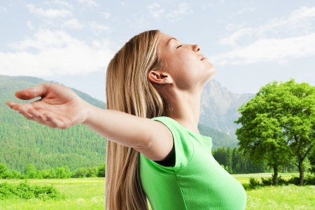 freedom girl: Relaxed young woman with arms outstretched, enjoying nature
