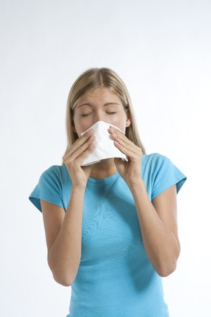 ah1n1: Young woman blowing her nose with kleenex, isolated on white