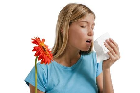 allerg�nes: Jeune femme soufflant son nez. Fleurs repr�sentant des allerg�nes saisonniers.