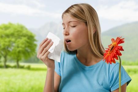 alergenos: Mujer joven soplar por su nariz. Flores que representan a los alergenos estacionales.  Foto de archivo