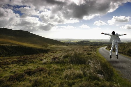 Man in wild scenery jumping raising his hands for freedom. Stock Photo - 7417505