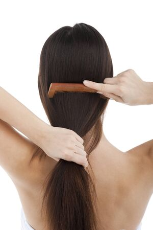 kam: Achteraanzicht van een vrouw die haar haren kammen