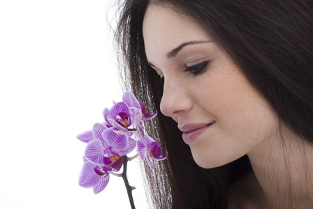 Beautiful young woman smelling flower photo
