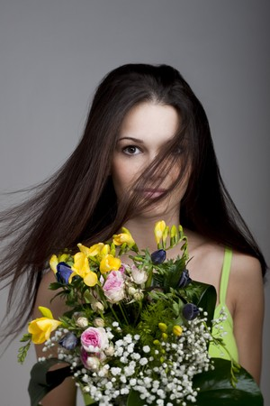 Beauty with a bunch of flowers, hair blowing in her face photo