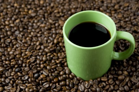 Coffee cup on coffee beans photo
