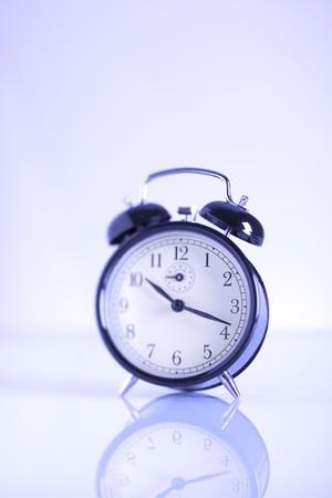 blue toned: Immagine tonica blu di un classico orologio sveglia, messa a fuoco differenziale