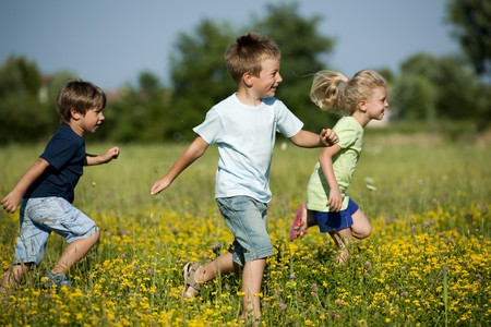 Three cute children running outdoors photo