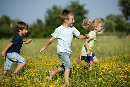 enfants qui jouent: Trois enfants mignons courir � l'ext�rieur Banque d'images