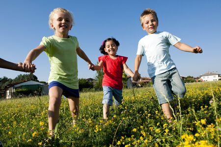 playground children: Three children running holding hands