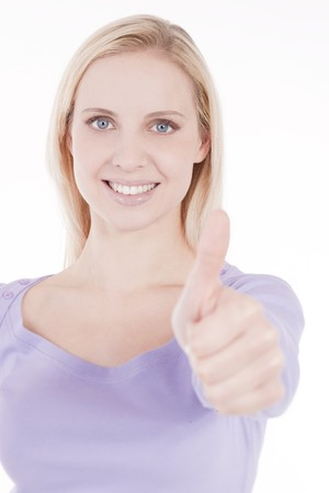 Beautiful young woman with thumbs-up, isolated on white; selective focus photo