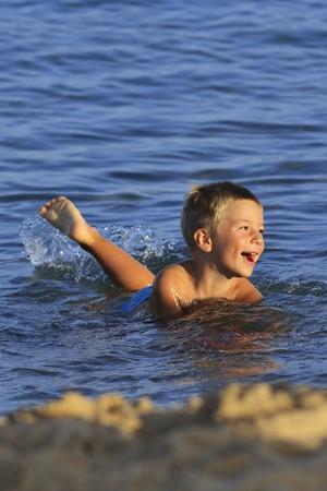 beach blond hair: Little boy having fun on the beach